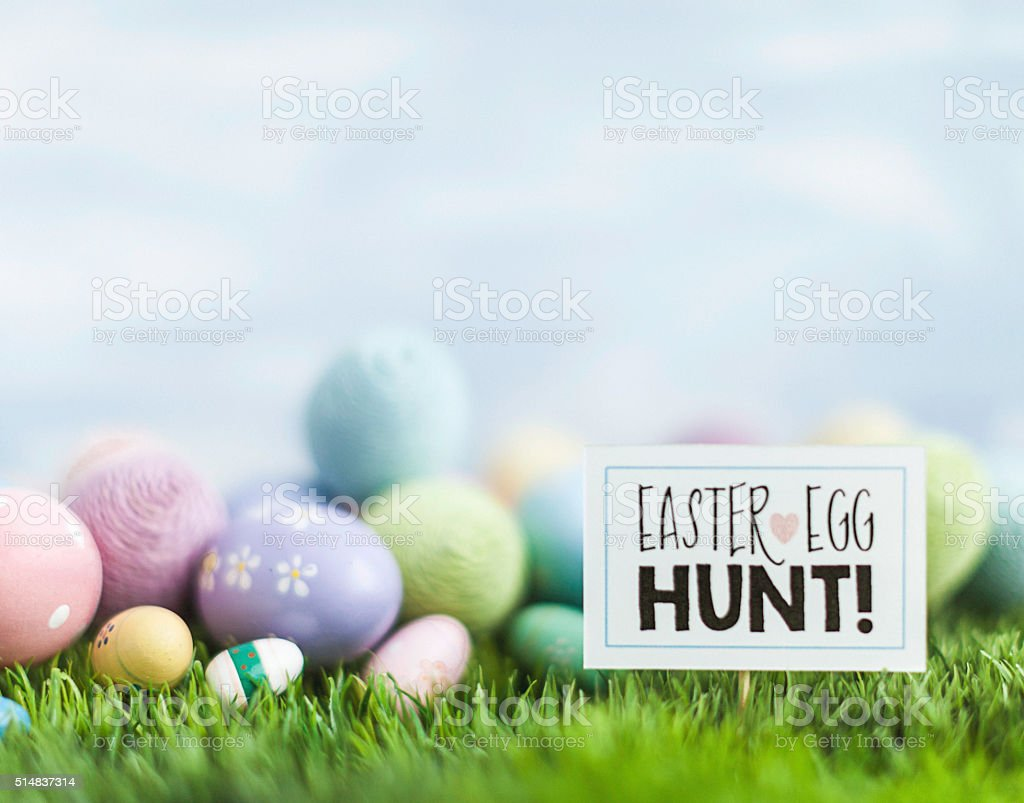 Easter egg hunt with variety of decorated eggs in background stock photo