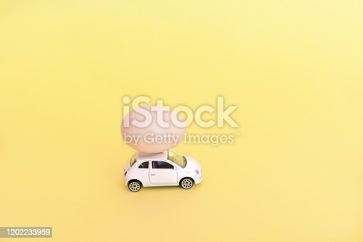 One Easter egg on a small car on a yellow background.  Happy easter day concept. Copy space.
