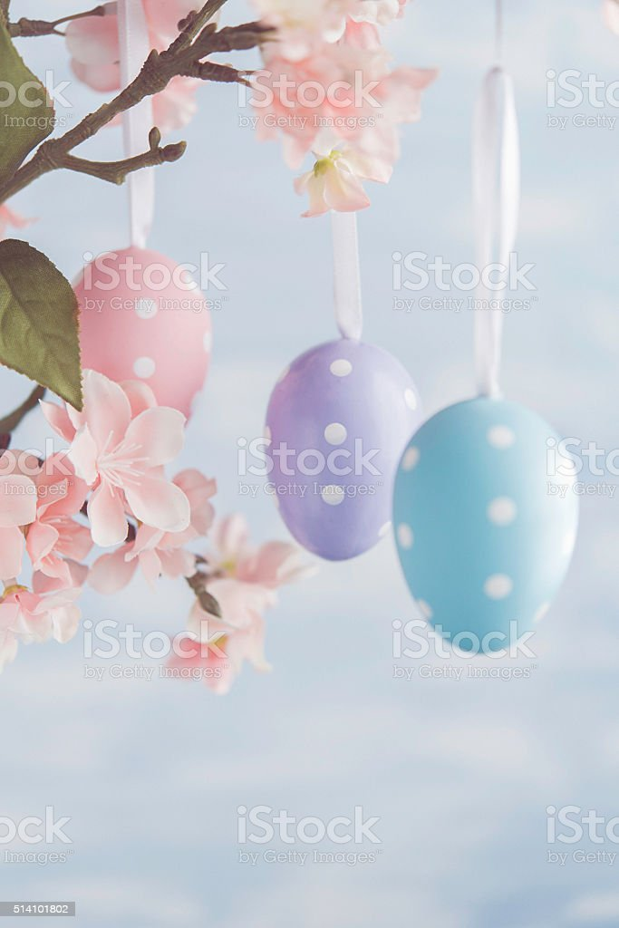 Easter egg shaped ornaments hanging on tree with blossoms stock photo