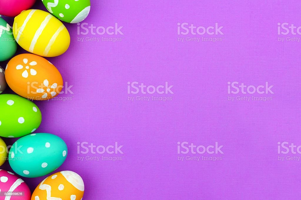 Easter egg side border over purple paper background stock photo