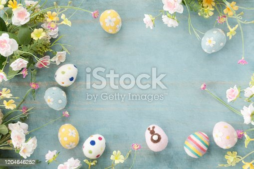 Easter Eggs and Flowers on a Rustic Textured Blue Wood Background