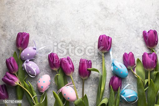 istock Easter eggs and lilac tulips on gray background. Top view flat lay. 1307924966
