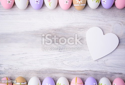 1136239089 istock photo Easter eggs and white heart on grey wooden background 513747148