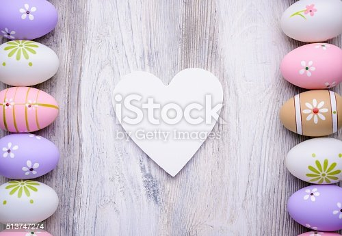 1136239089 istock photo Easter eggs and white heart on grey wooden background 513747274