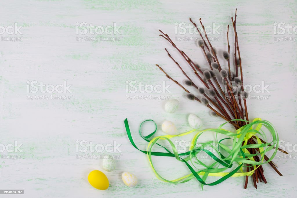 Easter eggs and willow tree branch with green ribbon stock photo