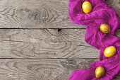Colorful Easter eggs and silk textile material on the wooden background. Festive Easter holiday concept. View from above. Copy space. Top view