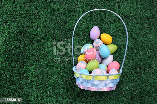 Easter eggs basket filled with colorful Easter eggs on green grass