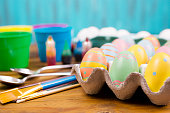 Happy Easter!   Easter Egg decorating supplies, preparation.  Decorated multi-colored easter eggs in carton, blank white eggs background, paint brushes, dye and cups, spoons.  The supplies all lie on a wooden table.   Preparation for an Easter Egg Hunt!   Great image for easter and spring themes.  No people. Pastel colors.  Crafts.