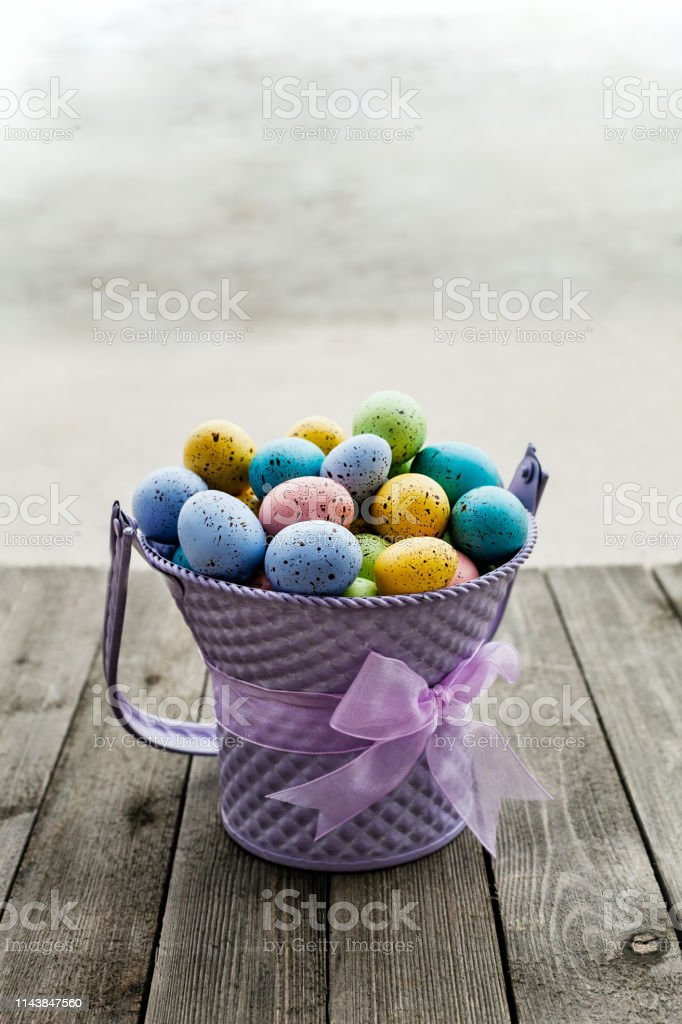 Easter eggs collected in a purple bucket with ribbon around, season holiday concept stock photo