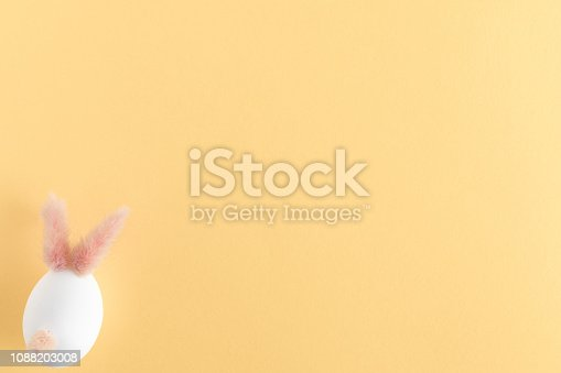930928526 istock photo Easter eggs cute bunny. Funny decoration on yellow pastel desk background. Happy Easter, top view and flat lay 1088203008