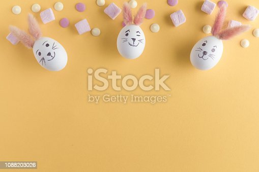 930928526 istock photo Easter eggs cute bunny. Funny decoration on yellow pastel desk background. Happy Easter, top view and flat lay 1088203026