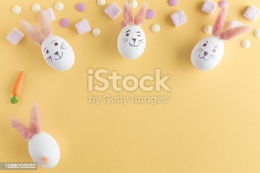 930928526 istock photo Easter eggs cute bunny. Funny decoration on yellow pastel desk background. Happy Easter, top view and flat lay 1088203032