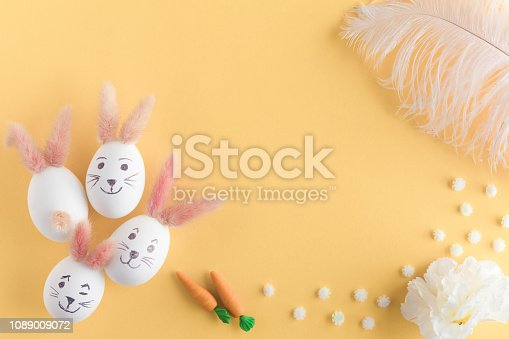 930928526 istock photo Easter eggs cute bunny. Funny decoration on yellow pastel desk background. Happy Easter, top view and flat lay 1089009072