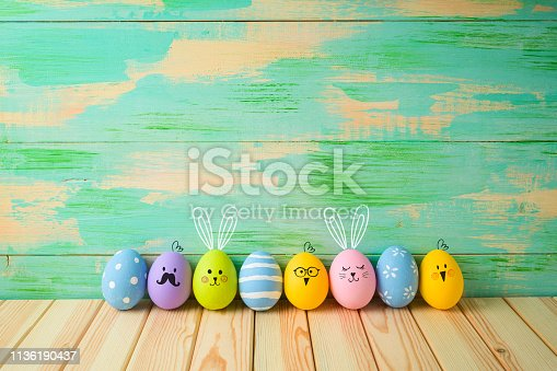 istock Easter eggs decorations on wooden table over colorful background 1136190437