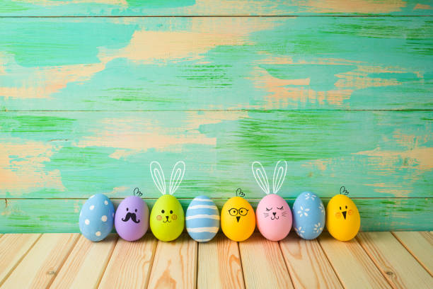easter eggs decorations on wooden table over colorful background - easter foto e immagini stock
