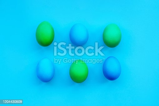 Easter flatlay with dyied on green and blue eggs isolated on bright blue background.