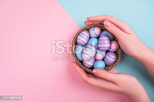 Woman hands holding dyed on blue, pink and violet Easter eggs in the straw basket isolated on blue background. Easter theme flatlay.