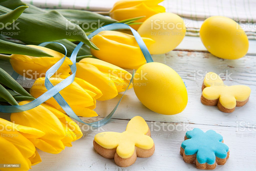 Easter eggs, homemade cookies and yellow tulips royalty-free stock photo