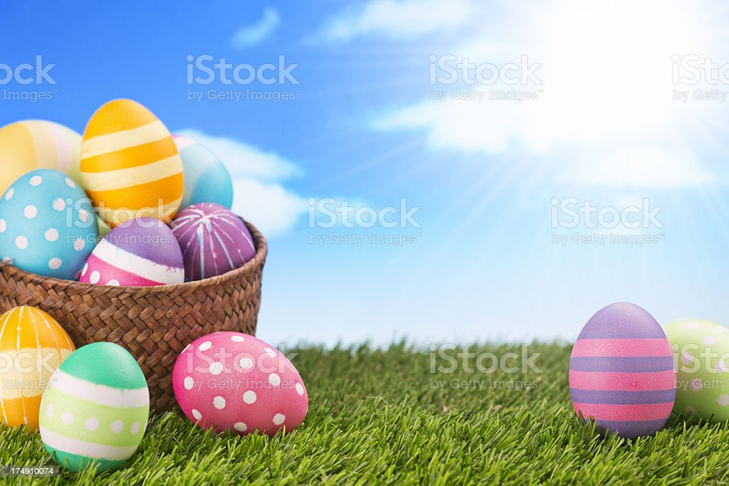 Easter eggs in a basket on a grassy field royalty-free stock photo