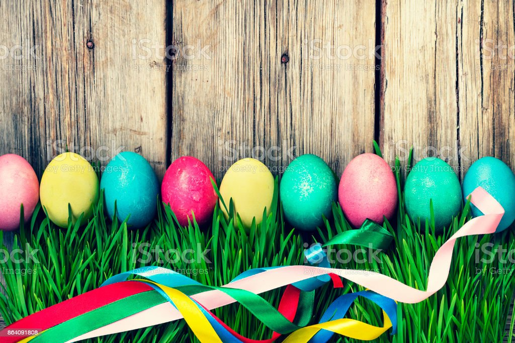 HAPPY EASTER Easter eggs in a green grass on a wooden background, authentic Easter decorations. royalty-free stock photo