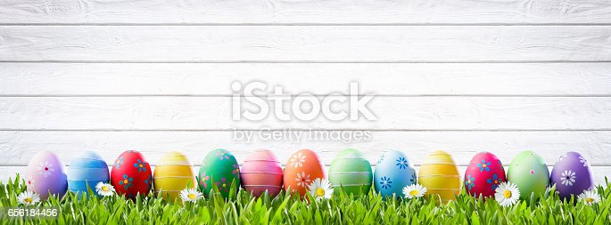 istock Easter Eggs In A Row And White Wooden Background 656184456
