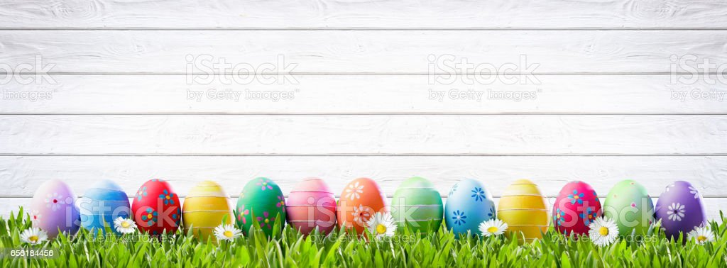 Easter Eggs In A Row And White Wooden Background stock photo