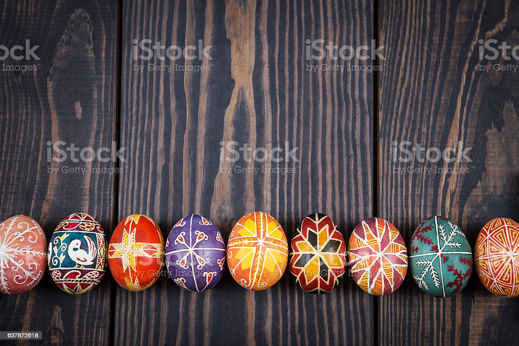 Easter eggs in a row on dark wooden background. stock photo