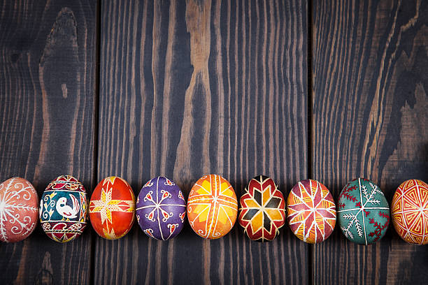 easter eggs in a row on dark wooden background. - ucrania fotografías e imágenes de stock