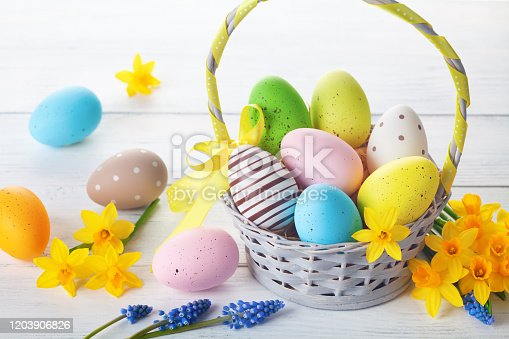 922843504 istock photo Easter eggs in basket and spring daffodil flowers on white wooden table. 1203906826