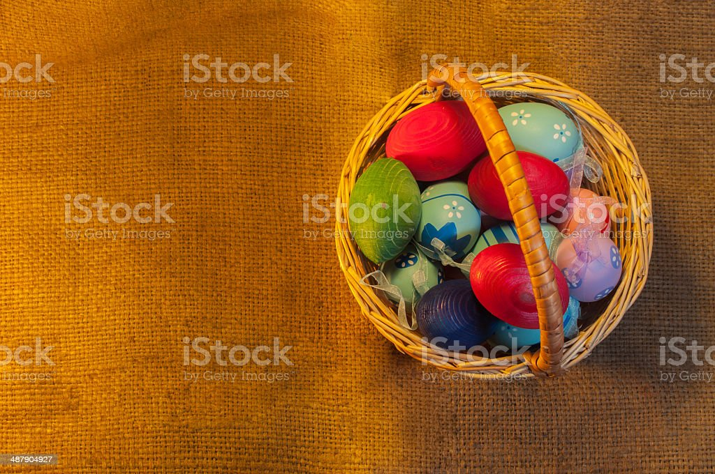 Easter Eggs in Basket on sackcloth background royalty-free stock photo