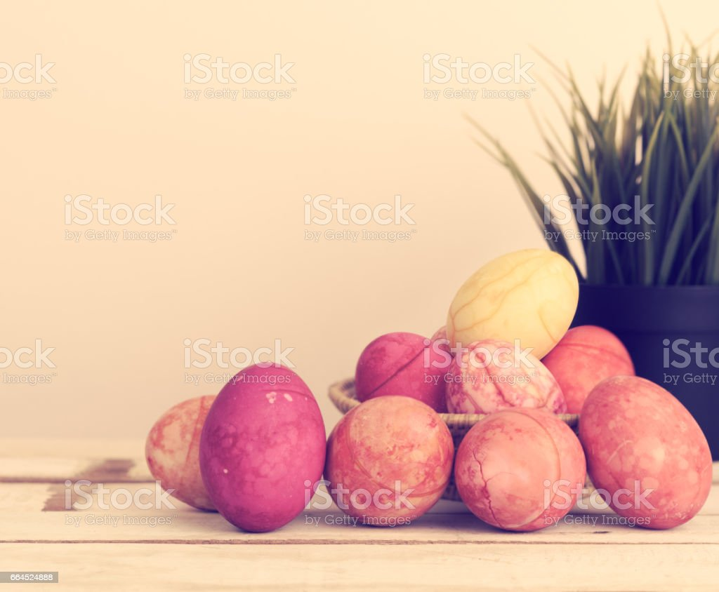 Easter eggs in basket on wooden table top with vintage house background,retro effect royalty-free stock photo
