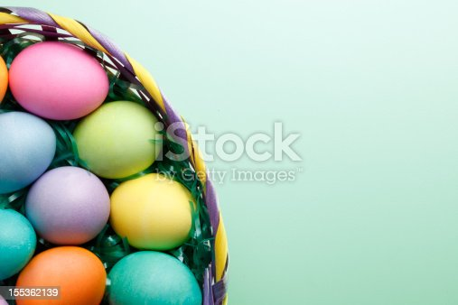 A top view of Easter eggs in an Easter basket on a pastel green background.