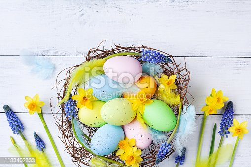 istock Easter eggs in nest, feather and spring flowers on white table top view. Holiday card or banner. 1133402333