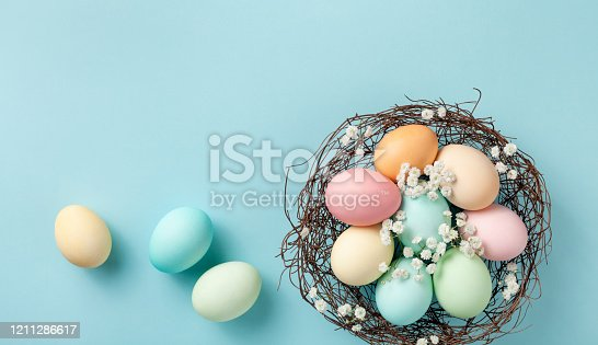 1138213028 istock photo Easter eggs in nest on blue pastel background top view. Modern flat lay. 1211286617