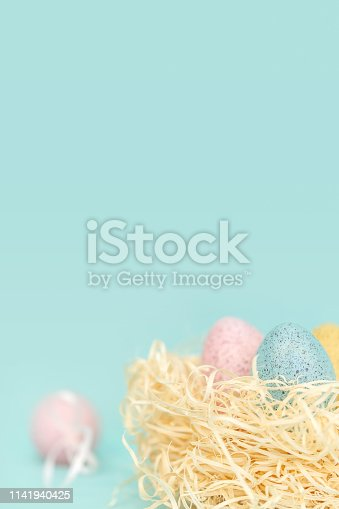 922658520 istock photo Easter eggs in nest on pastel background 1141940425
