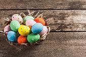 Easter eggs in nest on grunge wooden background