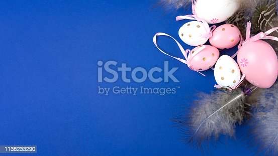 istock Easter eggs in pink and white on a blue background decorated with feathers and ribbons. 1138233290