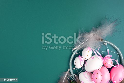 istock Easter eggs in pink and white on a green background decorated with feathers . 1140839747