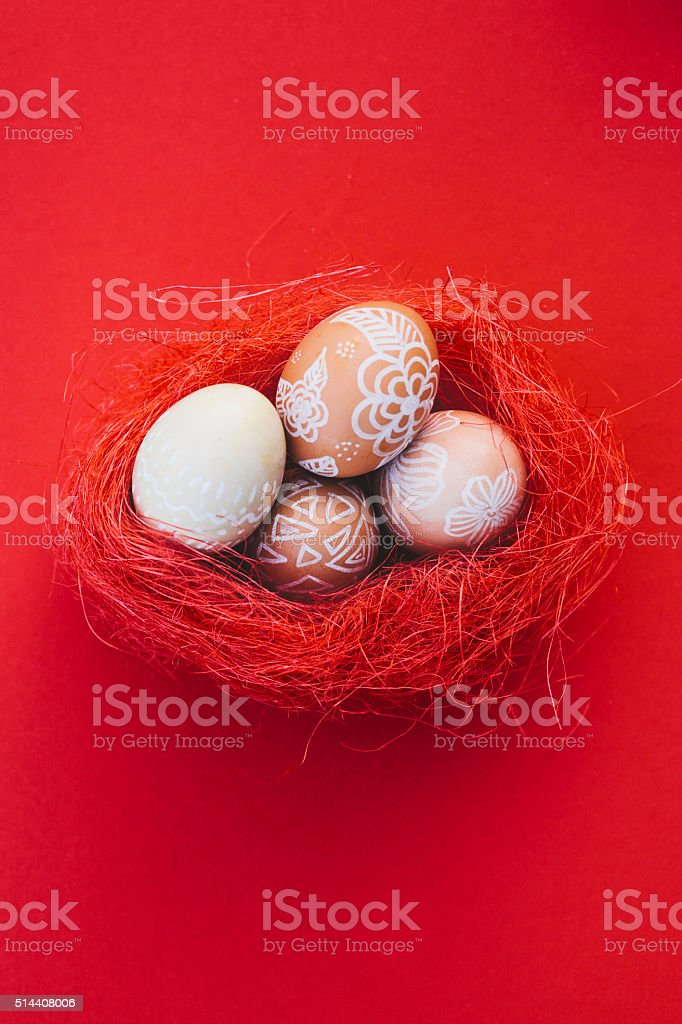 Easter eggs in red nest on red background stock photo