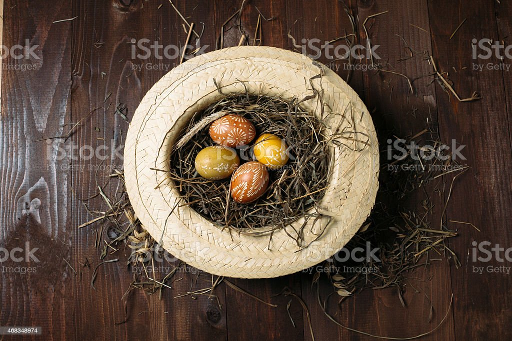 Easter eggs in straw on dark wooden background royalty-free stock photo