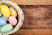 Happy Easter!  Close-up image of decorated multi-colored easter eggs lying in a white basket on a vintage wooden background. Ready for an Easter Egg Hunt!   Great frame for easter and spring themes.  No people. Pastel colors.  Copyspace to right.