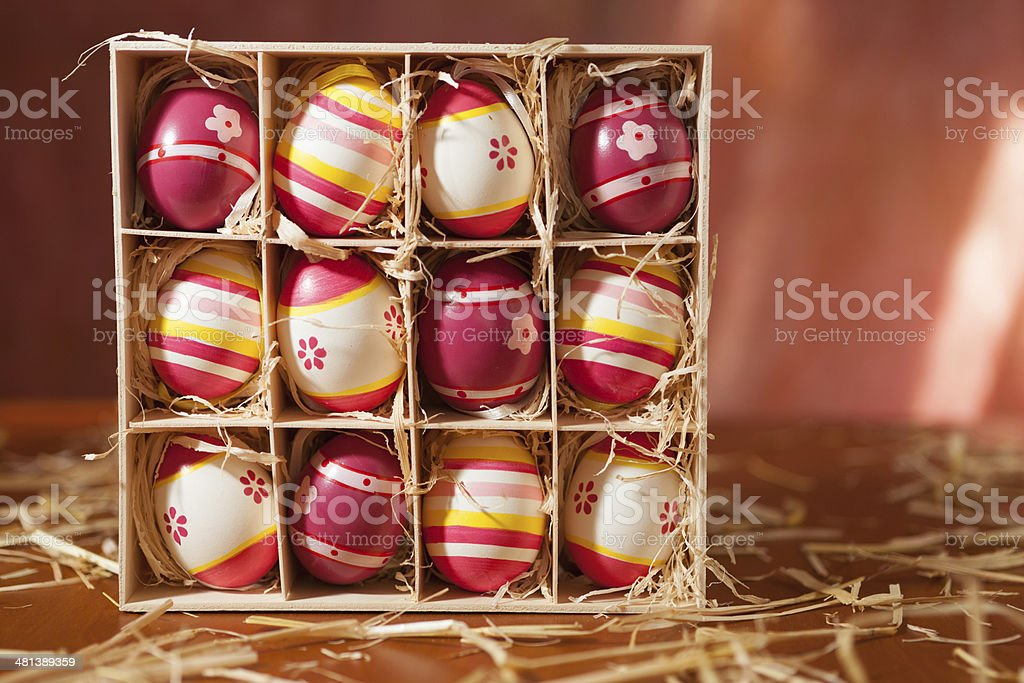 Rose, white, yellow decorated easter eggs in wodden box with straw