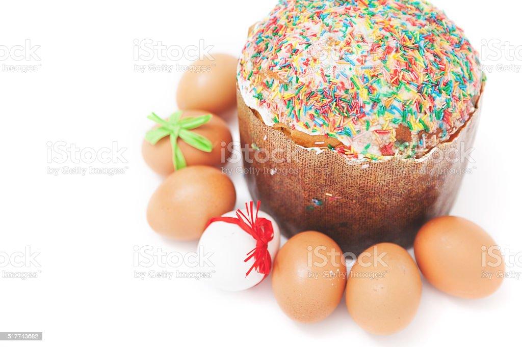 Easter eggs lie around cake on white background stock photo