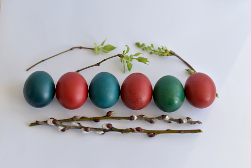 Easter eggs of various colors, willow branches lie in one row.