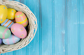 Happy Easter!  Close-up image of decorated multi-colored easter eggs lying in a white basket on a blue, vintage wooden background. Ready for an Easter Egg Hunt!   Great frame for easter and spring themes.  No people. Pastel colors.  Copyspace to right.