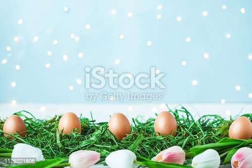 912300146 istock photo Easter eggs on green grass, tulips with bokeh and sunlight on a blue background Easter concept 1126221808
