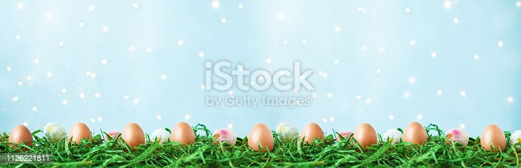 912300146 istock photo Easter eggs on green grass, tulips with bokeh and sunlight on a blue background Easter concept 1126221811
