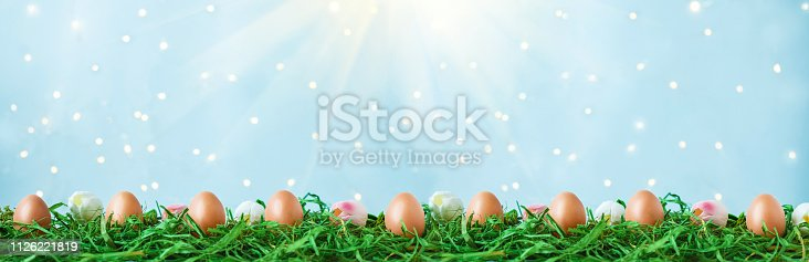 912300146 istock photo Easter eggs on green grass, tulips with bokeh and sunlight on a blue background Easter concept 1126221819