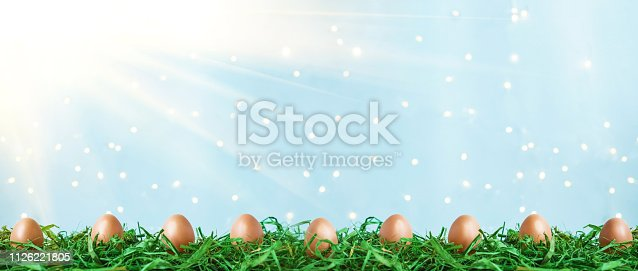 912300146 istock photo Easter eggs on green grass with bokeh and sunlight on a blue background Easter concept 1126221805