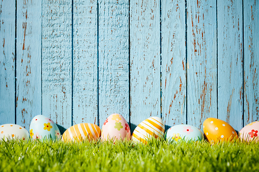 Close up photography of decorative multi colored easter eggs lying on vintage blue wood. Great for design for easter and spring related subject area. Photo captured with a Zeiss Makro-Planar T* 2/50mm at f8.
